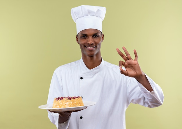 Young smiling afro-american cook in chef uniform holds cake on plate and gwstures ok sign with hand isolated on green wall