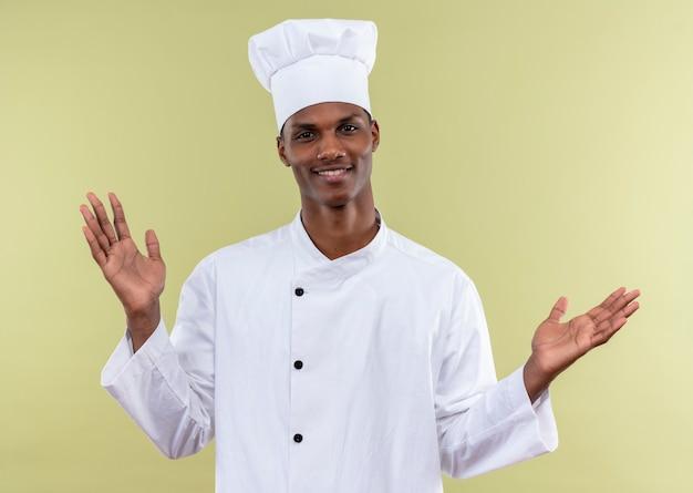 Il giovane cuoco afroamericano sorridente in uniforme del cuoco unico tiene le mani aperte isolate sulla parete verde