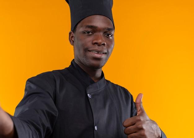 Il giovane cuoco afroamericano sorridente in uniforme del cuoco unico finge di tenere la macchina fotografica e il pollice in alto isolato su priorità bassa arancione con lo spazio della copia