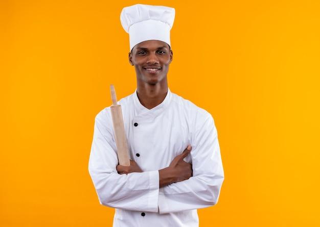 シェフの制服を着た若い笑顔のアフリカ系アメリカ人料理人が腕を組んで、オレンジ色の壁に隔離された麺棒を保持します。
