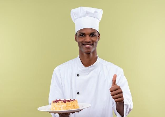 シェフの制服を着た若い笑顔のアフリカ系アメリカ人料理人は、プレートにケーキを保持し、緑の壁に隔離された親指を立てる