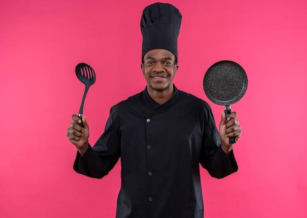 シェフの制服を着た若い笑顔のアフリカ系アメリカ人料理人は、ピンクの壁に分離されたフライパンとヘラを保持します