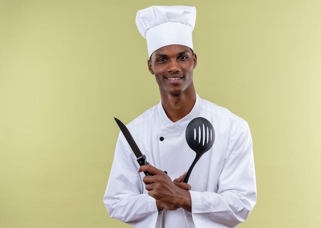 シェフの制服を着た若い笑顔のアフリカ系アメリカ人料理人は、緑の壁に分離されたナイフとヘラを保持します