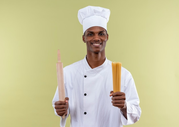 シェフの制服を着た若い笑顔のアフリカ系アメリカ人料理人は、緑の壁に隔離された手で麺棒とスパゲッティの束を保持します