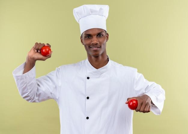 シェフの制服を着た若い笑顔のアフリカ系アメリカ人料理人は、緑の壁に隔離された両手にトマトを保持します