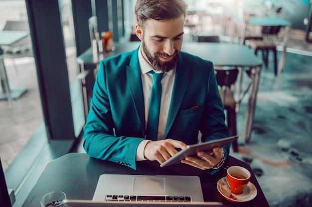 Молодой улыбающийся честолюбивый бородатый кавказских бизнесмен в формальных износа, сидя в кафе и с помощью планшета. на столе кофе и ноутбук. если вы усердно работаете на ралли, произойдут удивительные вещи.