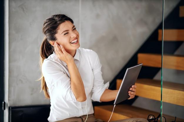 彼女のオフィスに座って、タブレットを介して電話会議をしている若い笑顔の建築家。