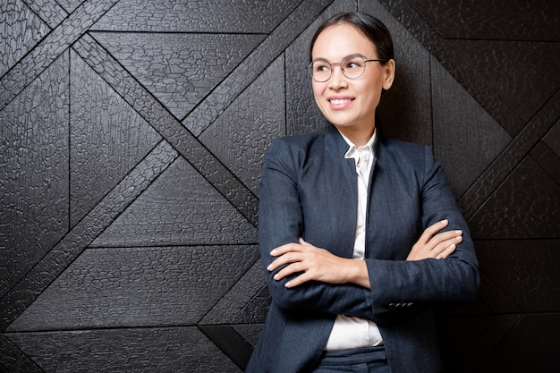 Young smiling asian businesswoman with crossed arms standing by black wooden wall of luxurious restaurant