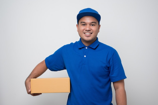 Young smiling asian delivery man in uniform holding box