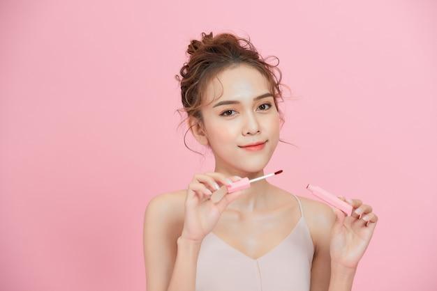 ピンクの背景に分離された口紅を適用する若い笑顔のアジアの女の子。