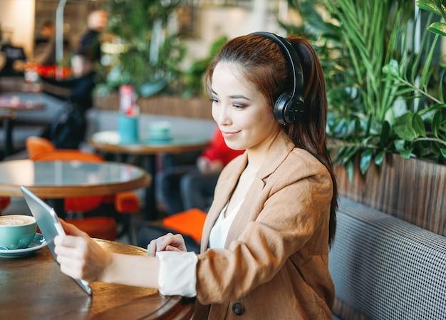 ヘッドフォンで若い笑顔のアジアの女の子の学生がタブレットで通信カフェで外国語を学ぶ