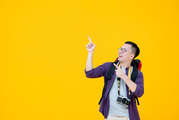 Young smiling asian  male backpacker looking up while pointing to copy space