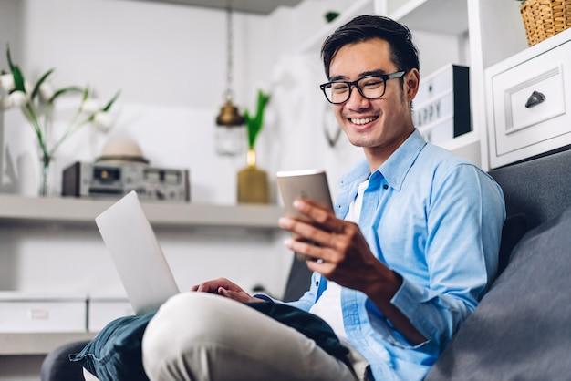 Человек детенышей усмехаясь азиатский ослабляя используя работу портативного компьютера и встречу видеоконференции дома. молодой творческий человек смотря сообщение экрана печатая с smartphone. работать из дома концепции