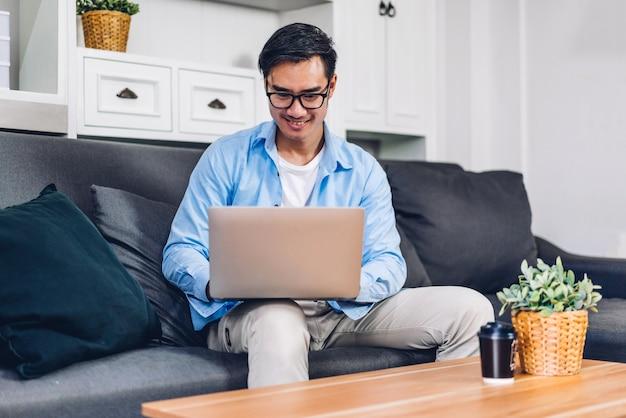 Молодой улыбающийся азиатский мужчина расслабляется с помощью портативного компьютера и работает в онлайн-чате для видеоконференции