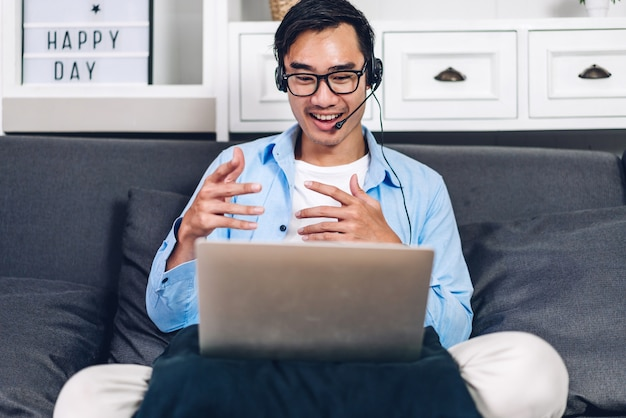 Young smiling asian man relaxing using laptop computer working and video conference meeting online chat at home