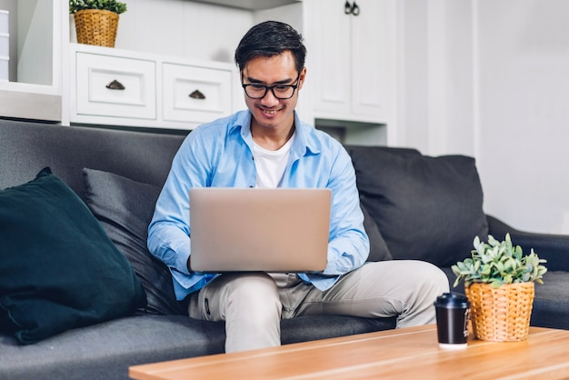 Young smiling asian man relaxing using laptop computer working and video conference meeting online chat
