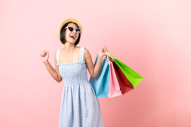 Young smiling asian woman casual clothes holding multi coloured shopping bags on light pink background.
