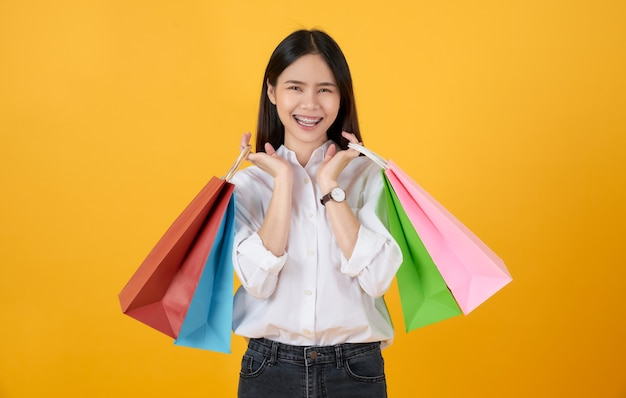 Молодая улыбающаяся азиатская повседневная одежда женщины, держащая разноцветные хозяйственные сумки