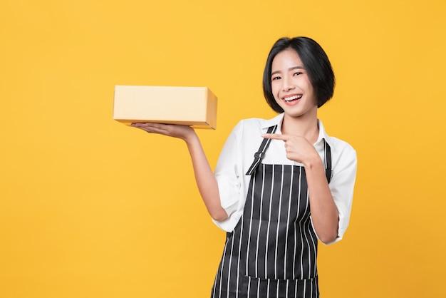 Женщина детенышей усмехаясь азиатская вручает показ картонных коробок и указывать на светлооранжевую стену