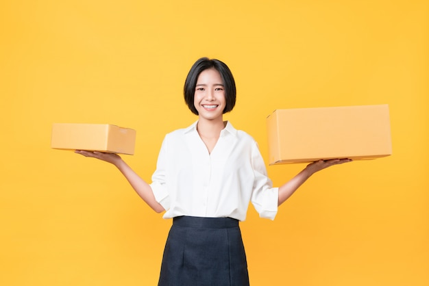 Young smiling asian woman hands showing cardboard boxes on light orange wall