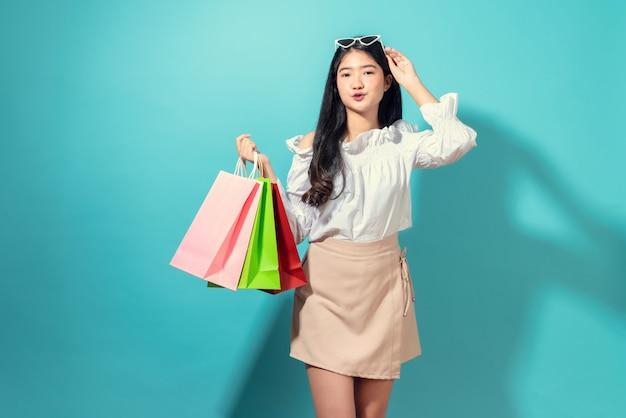 Молодая усмехаясь азиатская женщина держа multi покрашенные хозяйственные сумки и руки касается стеклам