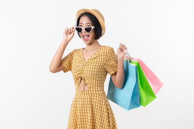 다양한 색상의 쇼핑백을 들고 흰색 배경을 바라보며 웃고 있는 젊은 아시아 여성.