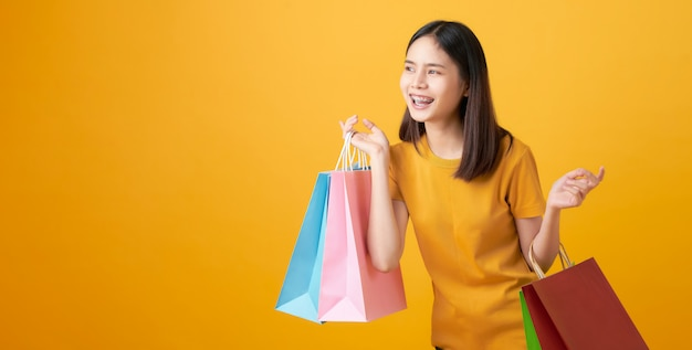 Young smiling asian woman holding multi coloured shopping bags and looking