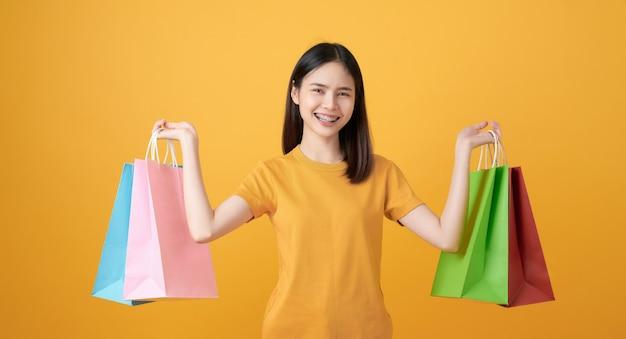 明るい黄色のマルチカラーの買い物袋を保持している若い笑顔のアジアの女性。