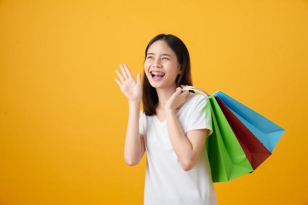 Молодая улыбающаяся азиатская женщина, держащая разноцветные хозяйственные сумки