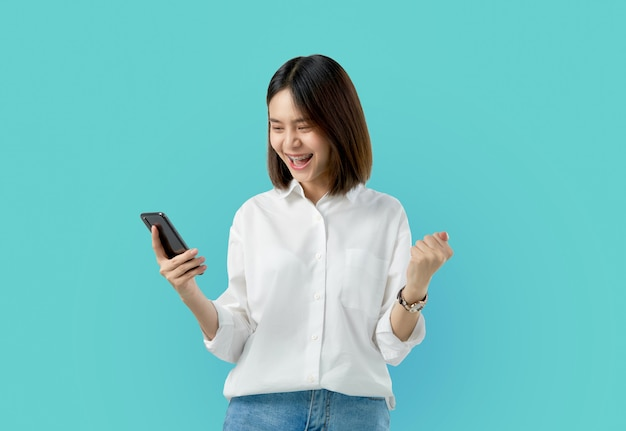 Young smiling asian woman holding smart phone with fist hand and excited for success on light blue