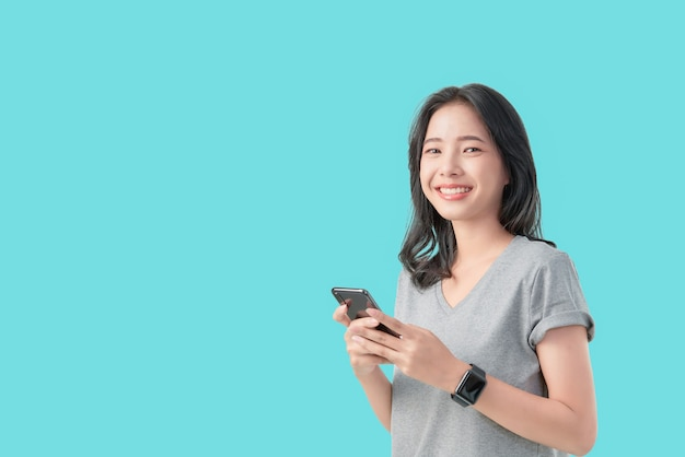 Young smiling asian woman holding smartphone and wear smartwatch isolated on light blue background.