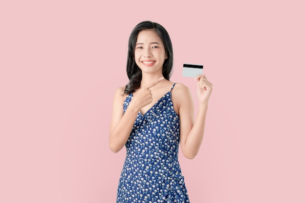 Young smiling asian woman pointing finger credit card blank