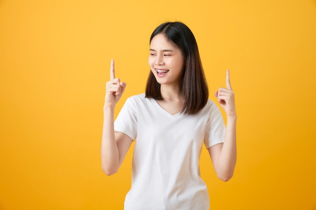 Молодая улыбающаяся азиатская женщина стоит и указывая пальцем