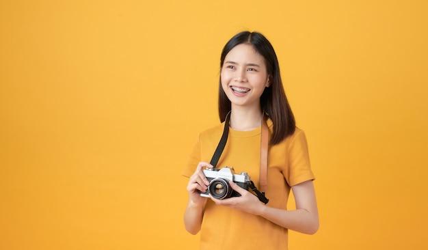 젊은 미소 아시아 여자 관광 카메라를 들고와 노란색 배경에 공간을 복사하고자합니다.