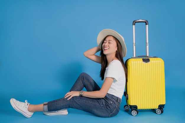 Young smiling asian woman traveler is happy sitting near yellow suitcase on blue