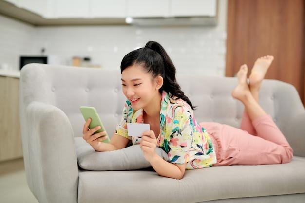 집에서 소파에 누워있는 동안 신용 카드로 온라인 쇼핑을 구매하는 스마트 폰을 사용 하여 젊은 미소 아시아 여자.