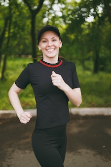 Young smiling athletic beautiful brunette girl in black uniform and cap training doing sport exercises, running and looking on camera on path in city park outdoors