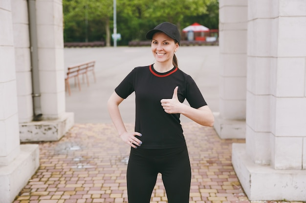 Young smiling athletic beautiful brunette woman in black uniform and cap doing sport exercises, warm-up before running, showing thumb up in city park outdoors