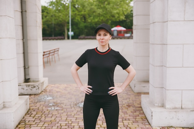 Young smiling athletic beautiful brunette woman in black uniform and cap doing sport exercises, warm-up before running, standing in city park outdoors