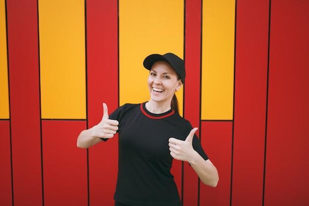 Молодая улыбающаяся спортивная красивая брюнетка женщина в черной униформе и кепке стоит и показывает палец вверх до или после тренировки на открытом воздухе на ярком фоне