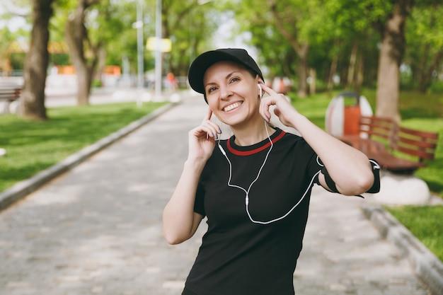 야외 도시 공원에서 훈련에 귀 근처에 손을 유지, 음악을 듣고 이어폰으로 검은 제복을 입은 젊은 웃는 운동 아름 다운 갈색 머리 여자와 모자