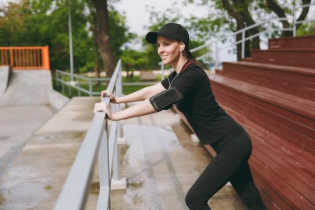 黒い制服を着た若い笑顔の運動の美しいブルネットの女性、屋外の都市公園でウォーミングアップスポーツストレッチ運動をしている音楽を聴いているイヤホンでキャップ