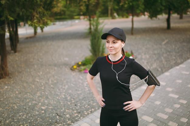 黒い制服を着た若い笑顔の運動の美しいブルネットの女性、スポーツエクササイズを行うヘッドフォンでキャップ、走る前にウォームアップ、屋外の都市公園に立っ