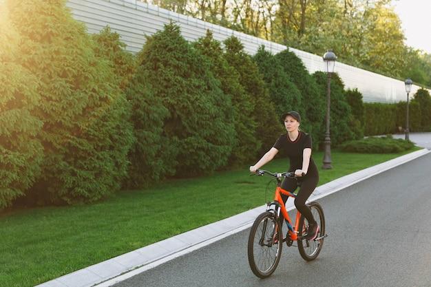 검은색 제복을 입은 젊고 웃는 운동 브루네트 강한 여성, 봄이나 여름 화창한 날 야외에서 주황색 요소가 있는 검은색 자전거를 타고 모자를 쓰고 있습니다. 피트 니스, 스포츠, 건강 한 라이프 스타일 개념입니다.