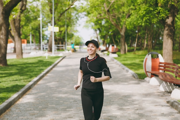 Young smiling athletic brunette woman in black uniform and cap with earphones training doing sport, running, jogging, listening to music on path in city park outdoors