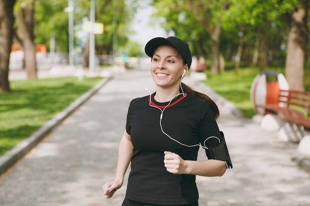 검은 제복을 입은 젊은 웃는 운동 갈색 머리 여자와 이어폰 훈련 스포츠, 달리기, 조깅, 야외 도시 공원에서 경로에 음악 듣기