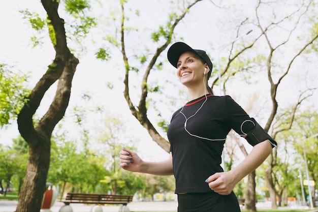 スポーツ、ランニング、ジョギング、屋外の都市公園の小道で音楽を聴くことを訓練するイヤホンで黒い制服と帽子の若い笑顔の運動ブルネットの女性