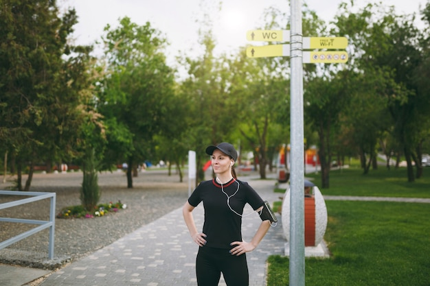 Young smiling athletic woman in black uniform, cap with headphones doing sport exercises, warm-up before running, standing in city park outdoors near signpost