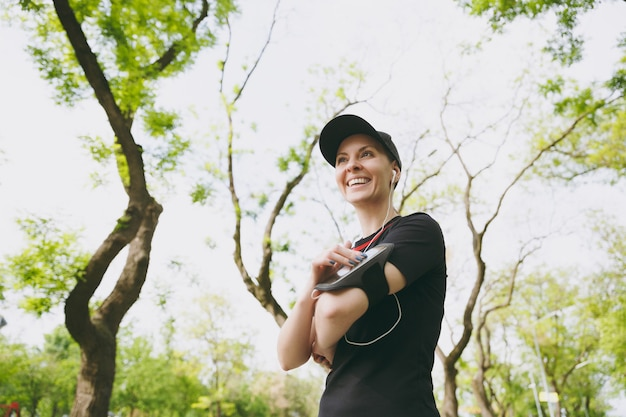 Young smiling athletic woman in black uniform with earphones listening to music, using application, app for running or jogging on mobile phone, training in city park outdoors
