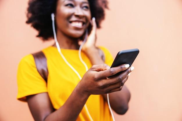 Молодая улыбающаяся привлекательная африканская женщина улыбается, слушает музыку и держит смартфон. селективный фокус под рукой.